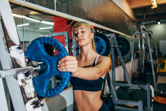Athletic girl sets weight on barbell in the gym Royalty Free Stock Photography