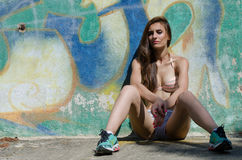 Athletic girl sitting against on the wall with graffiti. Athletic girl sitting against of a wall with graffiti wear cotton shorts and bra, beautiful and slim Stock Photos