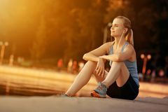 Athletic girl sitting by the lake after jogging. Royalty Free Stock Photos