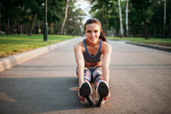 Athletic girl sitting on sidewalk in summer park Royalty Free Stock Image