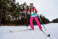 Athletic girl skiing in bright clothes. Young girl skiing in the winter woods. Bright make-up, clothes and ski goggles Royalty Free Stock Photo