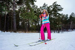 Athletic girl skiing in bright clothes. Young girl skiing in the winter woods. Bright make-up, clothes and ski goggles Stock Image