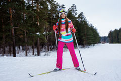 Athletic girl skiing in bright clothes. Young girl skiing in the winter woods. Bright make-up, clothes and ski goggles Royalty Free Stock Photos