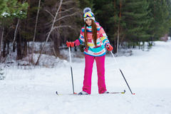 Athletic girl skiing in bright clothes. Young girl skiing in the winter woods. Bright make-up, clothes and ski goggles Stock Photography