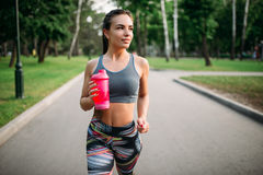 Athletic girl with sport bottle in summer park Royalty Free Stock Photo