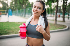 Athletic girl with sport bottle in summer park Stock Photography