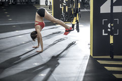 Athletic girl stands upside down in gym. Amazing girl stands on the hands upside down on the floor in the gym. Her feet are on the TRX straps. She wears red top stock photo