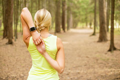Athletic girl stretching her arms. And getting ready to workout Royalty Free Stock Image