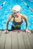 Athletic girl in the swim pool. Stylish female swimmer in the swimming pool. Woman wears a multi-colored swimsuit, a white swim cap and swim glasses. She looks stock photography