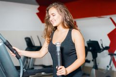 Athletic girl trains on the stepper simulator. woman in the gym smiling royalty free stock photo