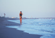 Athletic girl walking along the beach an amazing sunset with sea on background Royalty Free Stock Photos