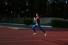 Athletic girl wearing sport apparel running at the empty stadium at the evening. Space for text royalty free stock image