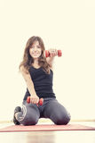 Athletic girl with weights or red dumbbells wearing sports clot Royalty Free Stock Images