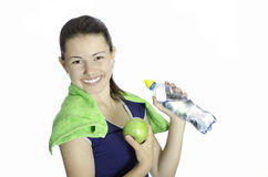 Athletic girl woman happy smiling. Athletic girl happy smiling holding apple and water bottle Stock Photos