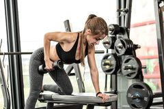 Athletic girl workout. Cute girl has a hard athletic workout in the gym, doing exercises with barbells royalty free stock images
