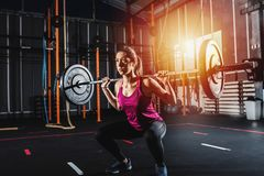 Athletic girl works out at the gym with a barbell Stock Image