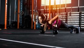 Athletic girl works out at the gym with a kettlebell Royalty Free Stock Image