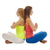 Athletic girlfriends posing sitting back-to-back Stock Photo