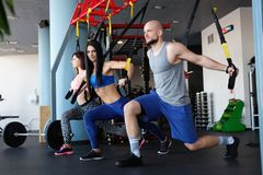 Athletic group doing crossfit training with functional loops in the gym. stock images