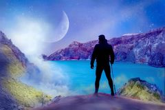 Athletic guy against the background of the alien landscape. Mountains, the lake and the moon. Concept Super Hero royalty free stock photos