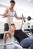 Athletic Guy Assisting Fit Girl Lifting Barbell Stock Photos