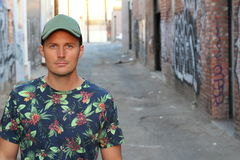 Athletic guy in a floral tee shirt and a baseball cap on urban background with copy space.  Royalty Free Stock Photography
