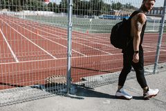 Athletic guy in headband dressed in black sport clothes with backpack on his shoulders walks along the playground fence stock photo