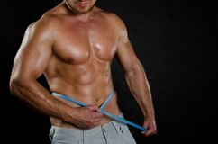 Sport and diet. Attractive man with muscular body. Athletic guy. Man measuring tape body Royalty Free Stock Image