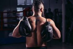 Guy back towards camera, pair of boxing gloves over his shoulder. Athletic guy with naked torso, back towards camera, pair of boxing gloves over his shoulder Stock Photo