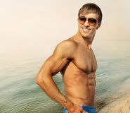 Athletic guy in sunglasses on the beach Royalty Free Stock Photography