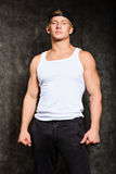 Athletic guy in a vest and  baseball cap. Athletic guy in a vest and a baseball cap on black background Royalty Free Stock Photo