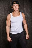 Athletic guy in a vest and  baseball cap. Athletic guy in a vest and a baseball cap on black background Royalty Free Stock Images