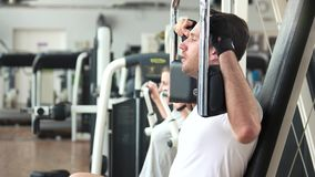 Athletic gym trainer doing chest press exercise. Young handsome man using exercise equipment at gym stock video