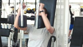 Athletic gym trainer doing chest press exercise. Young beautiful woman using exercise equipment at gym. Active way of life stock video footage