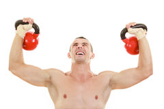 Athletic half naked man holding and lifting red kettlebells weig Royalty Free Stock Photo