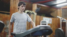 Athletic handsome man exercising and running on treadmill in sport gym. 1920x1080. Young athletic man exercising and running on treadmill in sport gym. 1920x1080 stock footage
