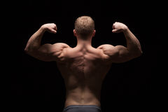 Athletic handsome man fitness-model showing his muscular back, isolated on black background with copyspace Stock Image