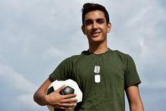 Athletic Hispanic Male Teen Soldier And Soccer. A young hispanic male teen Stock Photos