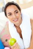 Athletic hispanic woman with a towel and an apple Stock Photo