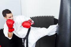 Athletic karate fighter giving a forceful foot kick to a heavy b Stock Image