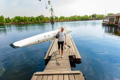 Athletic kayaker with his boat and paddle after rafting. Water leisure in summer. Active young oarsman standing on pier with his equipment, kayak and paddle stock photo