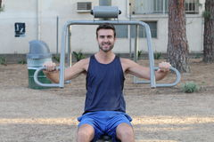 Athletic lean man executes exercise in outside sport gym.  Royalty Free Stock Photos