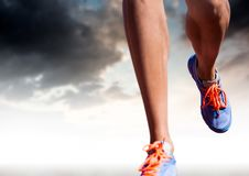 Athletic legs running in front of clouds Stock Photo