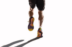 Athletic legs and running shoes of sport man jogging in fitness healthy endurance concept in advertising style. Rear view close up strong athletic legs and Stock Images