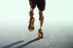 Athletic legs and running shoes of sport man jogging isolated in fitness healthy endurance concept in advertising style. Rear view close up strong athletic legs Stock Photos