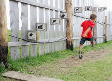 Athletic little boy makes a long jump in a rural playground Royalty Free Stock Images