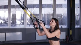 Athletic long haired woman workout out squats weighted lunges exercise with suspension straps in fitness club or gym stock video