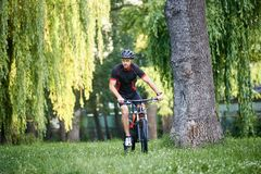 Male sportsman training on fresh air. Athletic male bicyclist riding bike through grass under green trees. Extreme training by man cyclist, getting redy for Royalty Free Stock Photo
