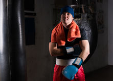 Athletic male boxer with a towel around his neck in a hat and bo. Xing gloves after training with boxing punching bag in a gym Royalty Free Stock Photo