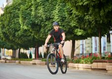 Male cyclist training in city center. Athletic male cyclist in cycling sportswear and protective gear, looking at camera, riding bicycle down empty city center Royalty Free Stock Image